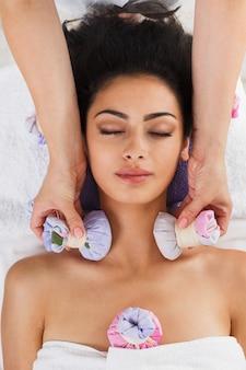 Woman has herbal ball massage in ayurveda spa wellness center