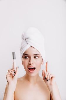 여성은 얼굴 톤을 개선하는 방법을 알고 있습니다. 손에 컨실러와 함께 아침 루틴 동안 여자의 초상화.