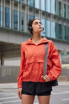 La donna ha un allenamento all'aperto porta un tappetino fitness per praticare esercizi di pilates con l'istruttore cammina contro il palazzo della città vestita con abbigliamento attivo ascolta brani dalla playlist