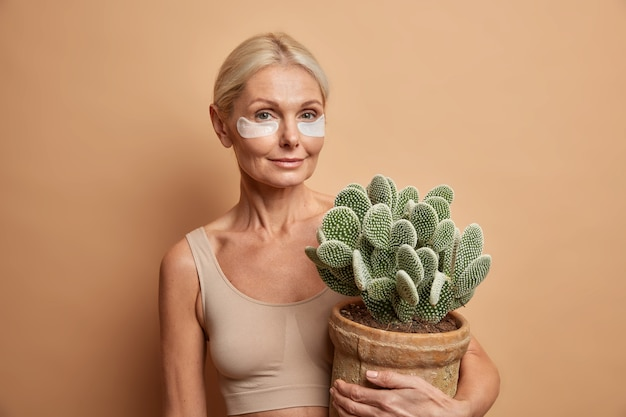 Woman has pefect facial skin aplies beauty pads under eyes to remove wrinkles holds pot of cactus isolated on beige