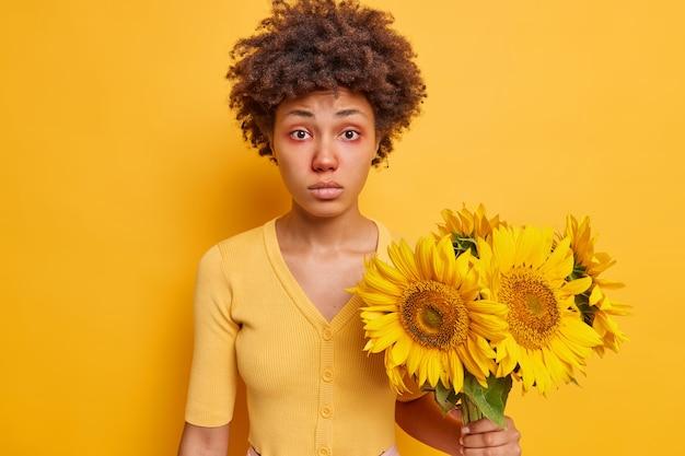 女性は目の周りに赤みがあり、ひまわりにアレルギーがあり、鮮やかな黄色のカジュアルなジャンパーポーズを着ています