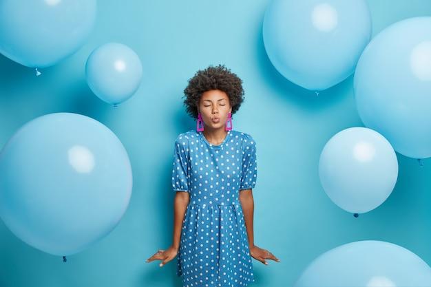 Woman has romantic mood keeps lips folded wears polka dot stylish dress want to kiss someone poses on blue