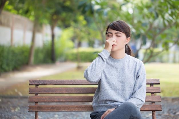 Женщина чихает в парке