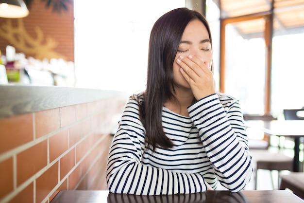 Женщина чихает в кафе