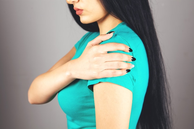 A woman has a sore shoulder on a gray background