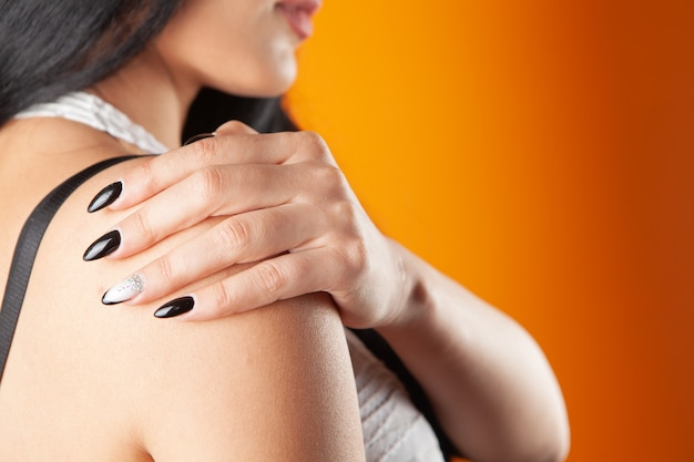 A woman has a sore shoulder on a orange background
