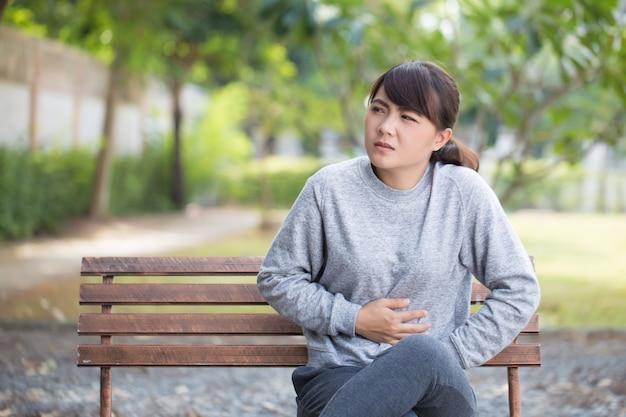 女性は公園で腹痛を持っています