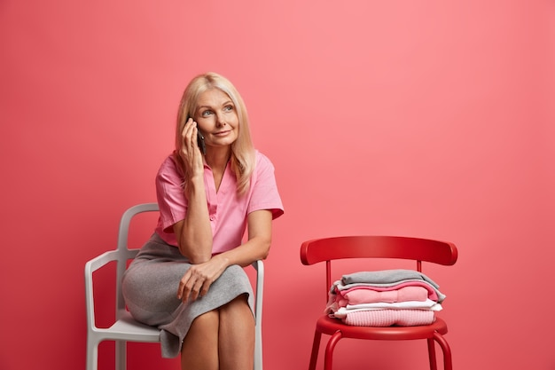 La donna ha una conversazione telefonica discute qualcosa ha un'espressione sognante posa su una sedia comoda trascorre il tempo libero a casa isolata sul rosa