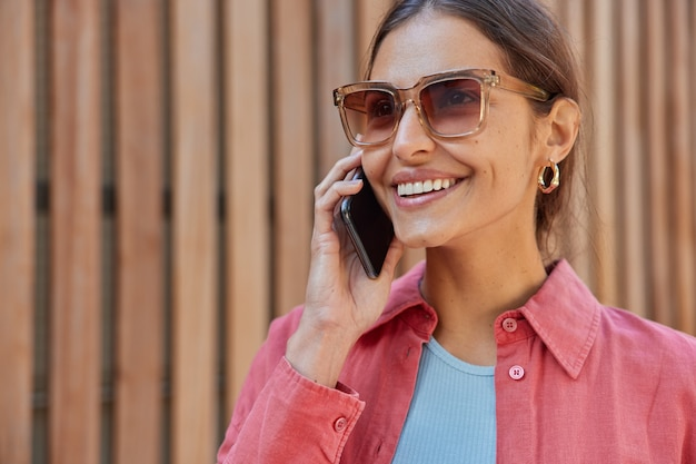 Woman has telephone conversation wears trendy sunglasses and pink shirt feels happy smiles broadly poses on hence communicates via smartphone application