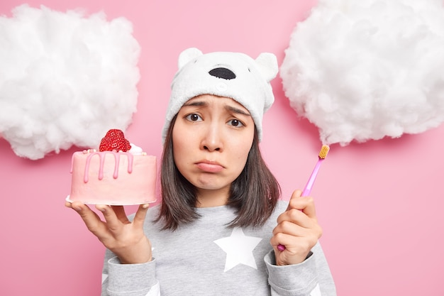 Woman has temptation to eat tasty sweet cake but afraids of having problems with teeth holds toothbrush