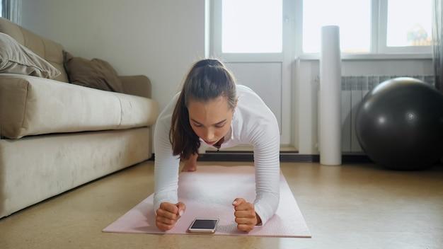 女性は部屋で電話でチュートリアルを見ているトレーニングを持っています