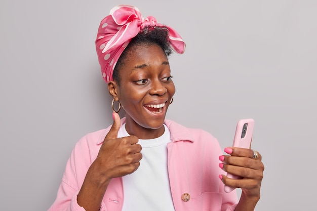 Woman has video call shows like sign at camera keeps thumb up holds modern smartphone dressed in stylish clothes isolated on grey