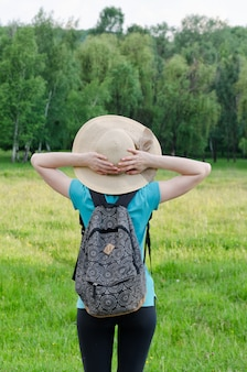 Woman in hat and backpack holds hands behind the head