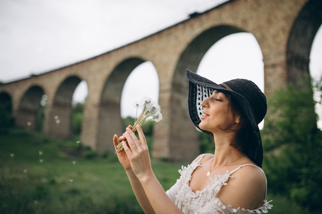 Woman in hat by railroad bridge with dandelion