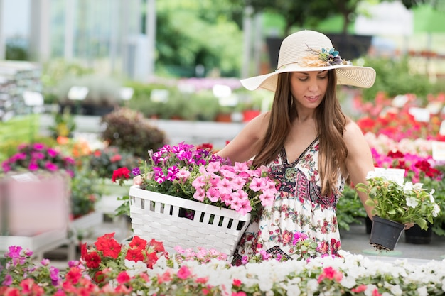 Woman in hat and dress holding flower basket
