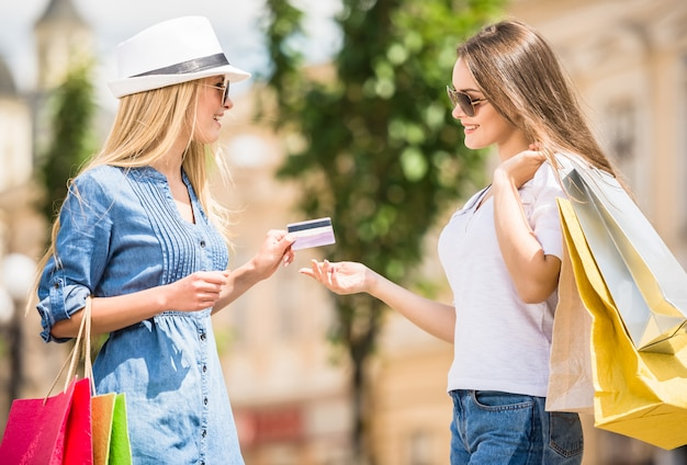 Woman in hat giving credit card to brown hair woman.