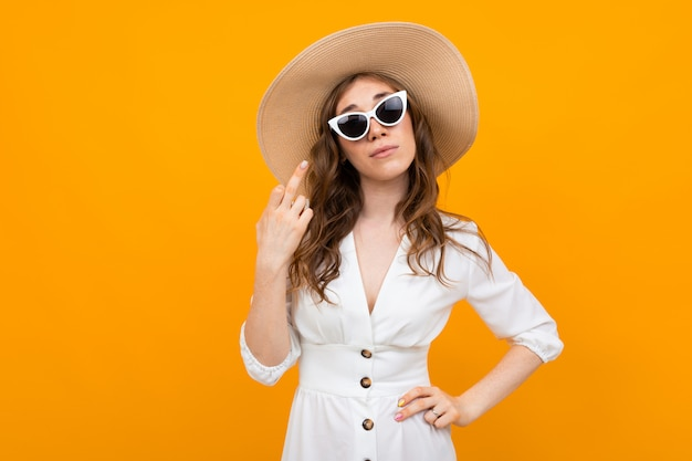 Woman in a hat and glasses you a white dress shows a middle finger