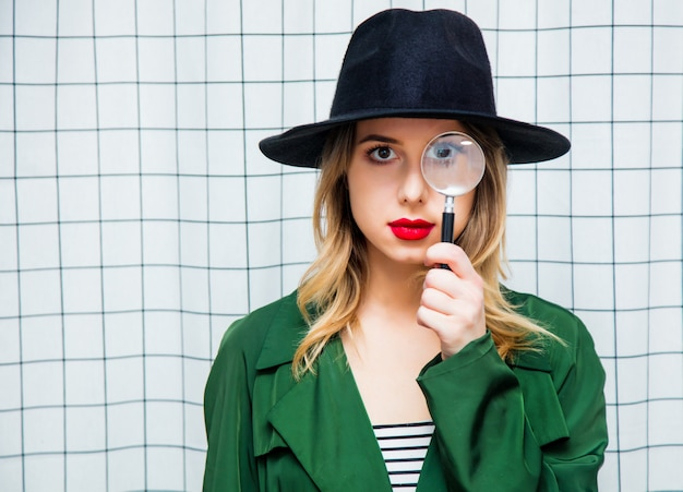 Woman in hat and green cloak in 90s style with magnifie