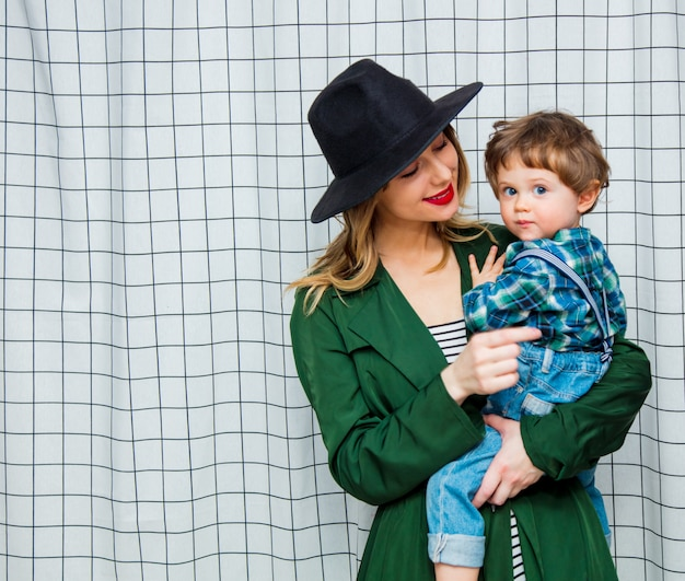 Woman in hat and green cloak in 90s style with toddler boy