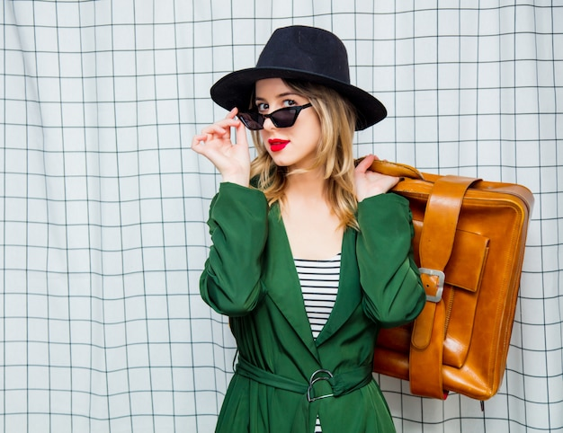 Woman in hat and green cloak in 90s style with travel suitcase