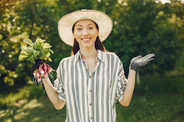 Donna in un cappello che tiene ravanelli freschi