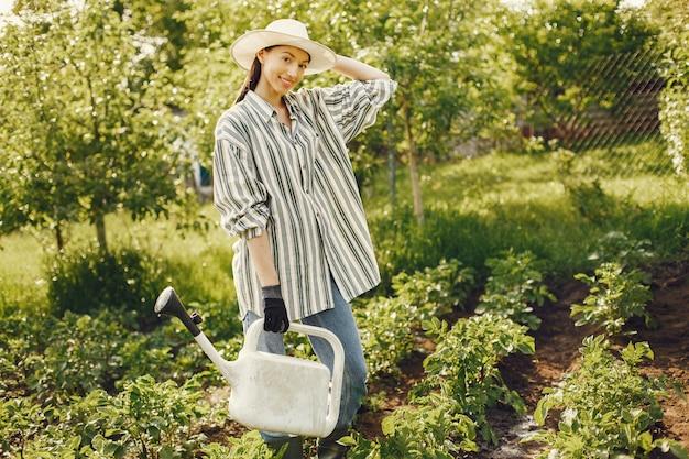 La donna in un cappello che tiene imbuto e lavora in un giardino