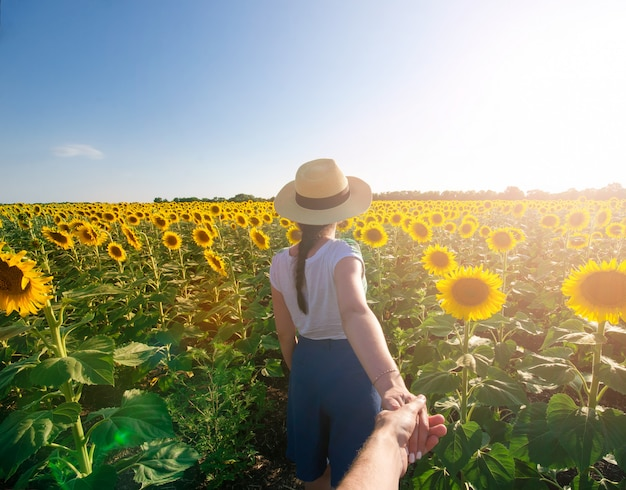 Woman in hat is holding man by hand going to sunflower field. traveling together. follow m
