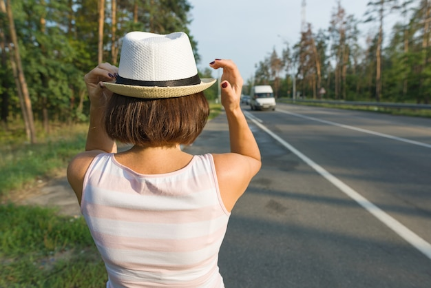 Woman in hat, looking forward to the road, copy space