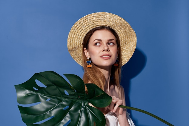Woman in hat palm leaves travel summer exotic blue background. high quality photo