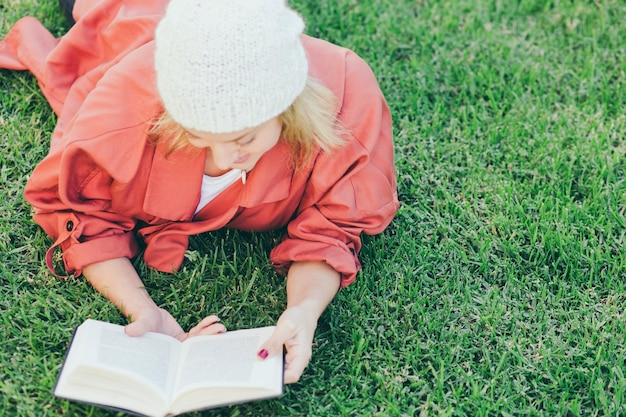 Woman in hat reading book on grass