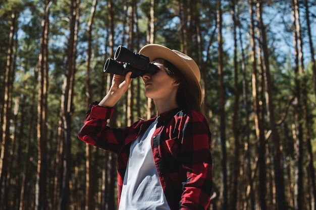 Woman in hat and red plaid shirt looking through binoculars in the forest.