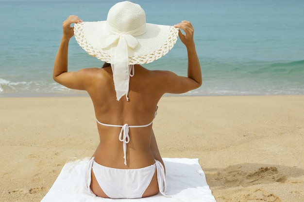 Woman in hat sitting on the beach