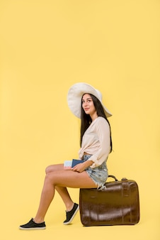 Woman in hat sitting on brown suitcase