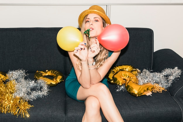 Woman in hat sitting on couch with balloons