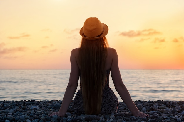 Woman in the hat sitting on the seashore. sunset time. silhouette.