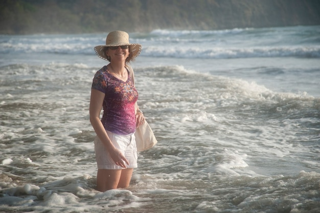 Woman in a hat smiling standing in the ocean surf at knee height