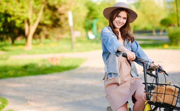 Woman in hat standing and smiling with bicycle outdoors in summer city
