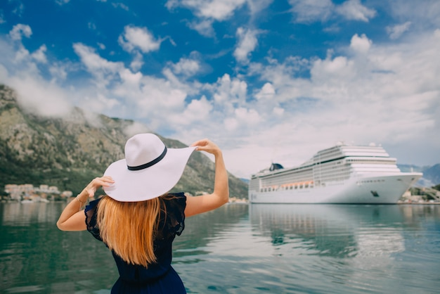 Woman in hat stands on cruise liner background, rear view