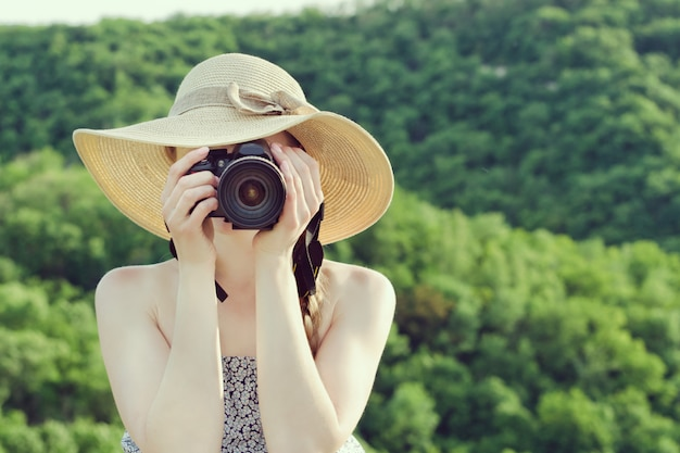 Woman in hat takes pictures against the green forest. front view