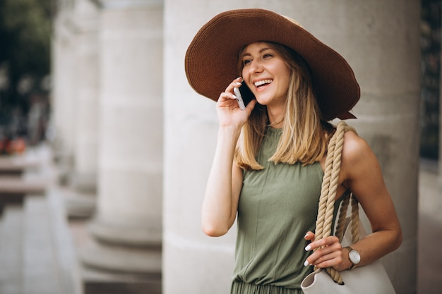 Woman in hat on vacation talking on the phone