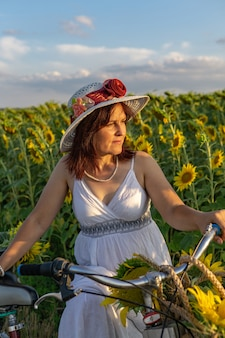 A woman in a hat and a white dress with a bicycle walks through the pollen with sunflowers