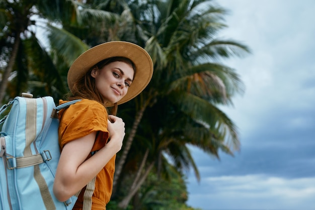 A woman in a hat and with a backpack smiles at the camera on the nature on the island