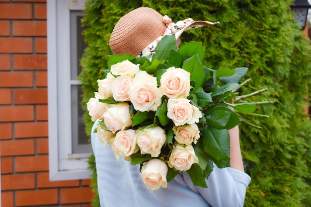 Woman in hat with a bouquet of flowers.