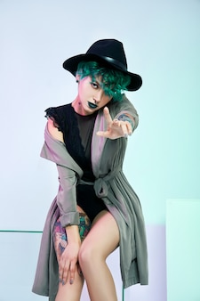 Woman in hat with creative green coloring hair and makeup, toxic strands of hair