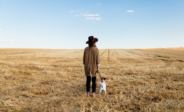 Woman in hat with dog on field