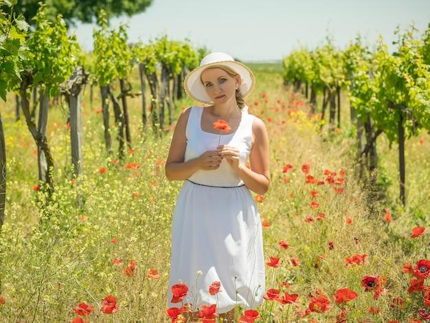 Woman in a hat with poppy flower on a grape field.