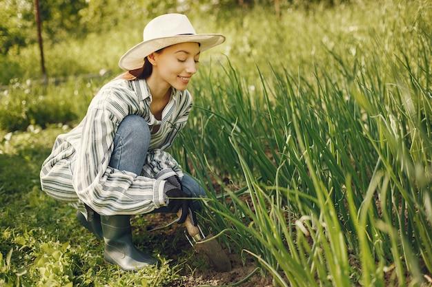 La donna in un cappello che lavora in un giardino