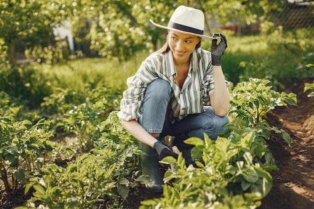 Woman in a hat working in a garden