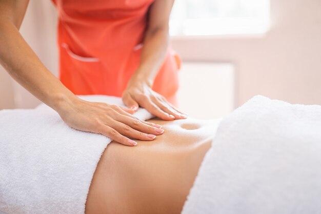 Женщина делает массаж живота в комнате для легких процедур. антицеллюлитный массаж, диастаз.