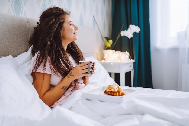 女性は明るいホテルのアパートのベッドで、または自宅で朝食をとります。クロワッサンを食べて、コーヒーを飲むウィンドウライトの肖像画の少女。